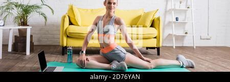 Photo panoramique de sportswoman s'étendant près d'un ordinateur portable sur un tapis de fitness à la maison Banque D'Images
