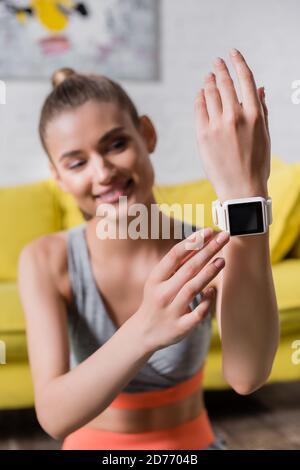 Mise au point sélective de la sportswoman souriante touchant la montre intelligente à la maison Banque D'Images