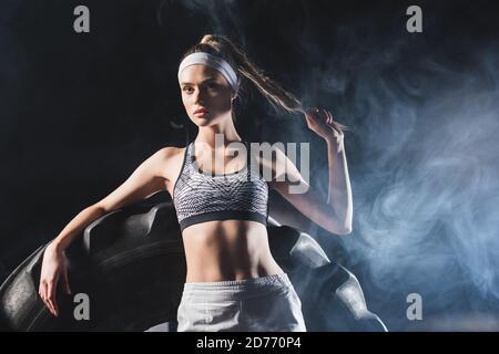 Mise au point sélective de sportswoman touchant les cheveux près du pneu dans le sport centre avec fumée Banque D'Images