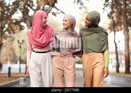 Trois musulmanes portant le hijab et des vêtements modernes marchant à l'extérieur