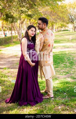 Jeune femme enceinte asiatique indienne avec son mari portant une tenue traditionnelle debout dans un parc ou un jardin pour écrire du texte.