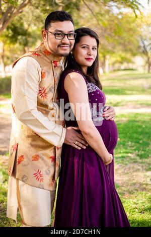 Jeune femme enceinte asiatique indienne avec son mari portant des vêtements traditionnels tenue debout dans le parc ou le jardin