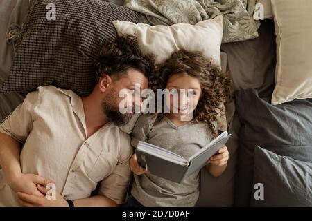 Bonne famille. Le père met sa fille au lit. Lecture avant le lit. Il est temps de vivre une histoire magique. Passez du temps ensemble. Papa et fille à la maison Banque D'Images