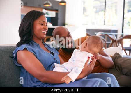 Souriant parents afro-américains se câliner et jouer avec bébé fille À l'intérieur sur canapé à la maison Banque D'Images