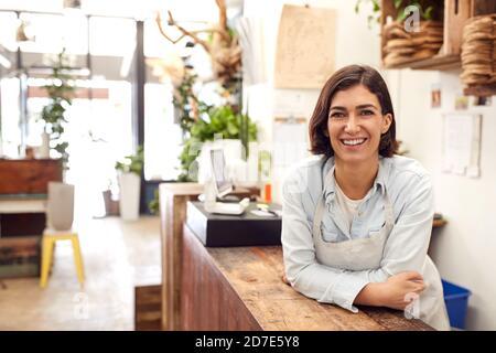 Portrait d'une femme sourit, sous le comptoir des ventes Du magasin Florists Banque D'Images