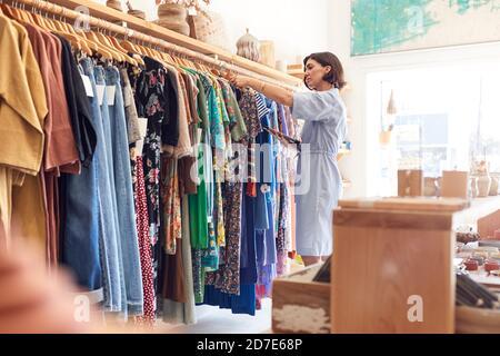 Femme propriétaire d'un magasin de mode utilisant une tablette numérique pour vérifier Stock sur rails dans le magasin de vêtements Banque D'Images