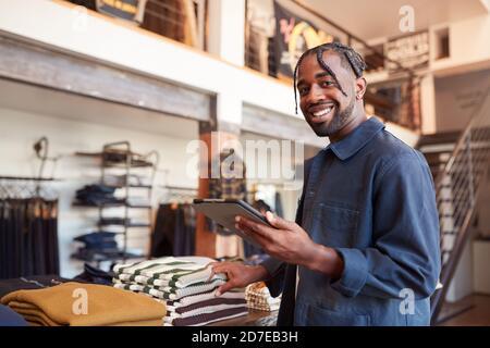 Portrait du propriétaire masculin de Fashion Store à l'aide d'une tablette numérique Pour vérifier le stock dans le magasin de vêtements Banque D'Images