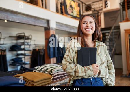 Portrait de la femme propriétaire de Fashion Store à l'aide d'une tablette numérique Pour vérifier le stock dans le magasin de vêtements Banque D'Images