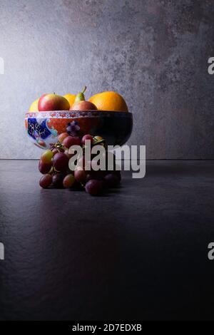 Bol de fruits avec pommes, poires, raisins et oranges.