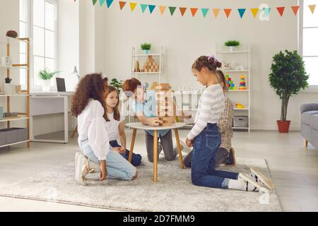 Groupe d'enfants divers assis sur le sol et jouant à un jeu de société avec des blocs de bois à la maison.