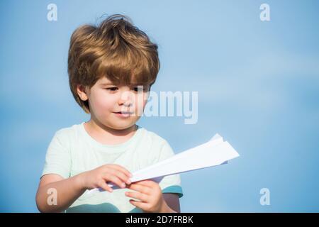 Concept de la parentalité et de l'enfance. Rêves de voyage. Joyeux enfant sur le terrain d'été - rêve de voler concept. Enfant heureux. Mignon garçon avec papier aipplène.