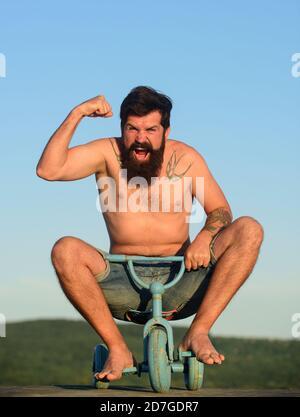 Guy tricycle d'équitation pour enfants. Drôle d'homme sur un vélo pour enfants. Vélo nerdy.