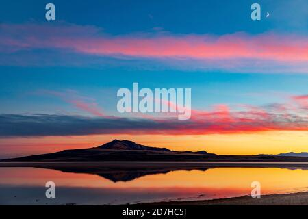 L'image de l'île d'Antelope se reflète sur l'eau du Grand Lac salé tandis que l'incandescence résiduelle du coucher de soleil se reflète dans les nuages au-dessus.