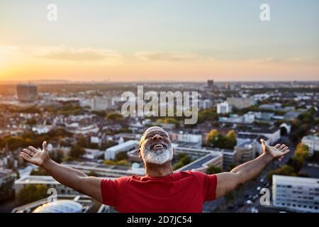 Homme à barbe heureux avec les bras étirés tout en se tenant debout sur le bâtiment terrasse en ville au coucher du soleil