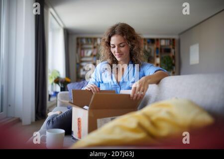 Femme ouvrant la boîte tout en étant assise sur le canapé à la maison