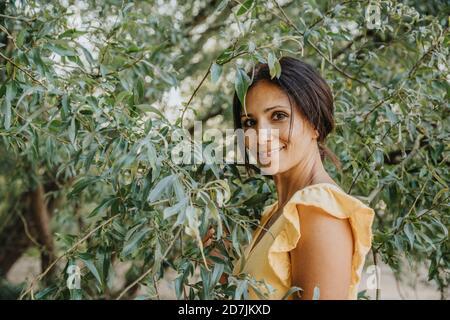 Femme mature debout sous un saule Banque D'Images