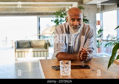 Homme bald confiant avec les mains clastées s'inclinant sur la table à sur le toit