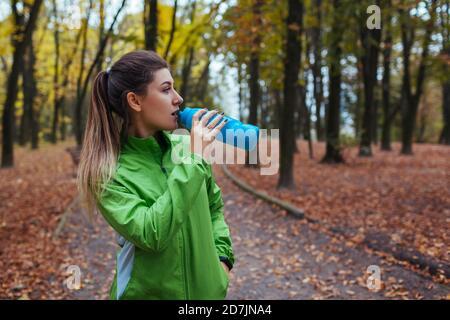Coureur se reposer après l'entraînement dans le parc d'automne. Femme buvant de l'eau. Style de vie actif sportif