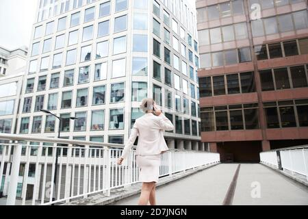 Femme entrepreneur parlant par téléphone mobile tout en marchant sur la passerelle dans le quartier du centre-ville