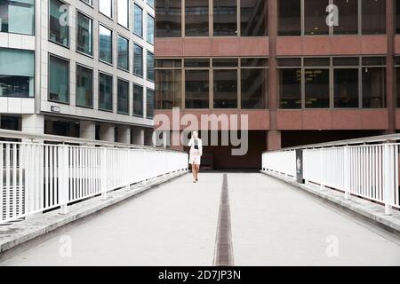 Femme d'affaires mûre parlant au téléphone intelligent tout en marchant sur la passerelle contre un immeuble de bureaux dans le quartier du centre-ville