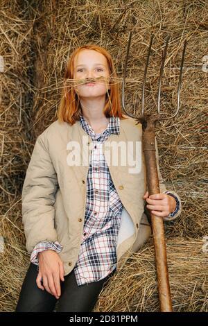 Petite fille de gingembre drôle faisant la moustache avec les lames de foin à l'intérieur une grange