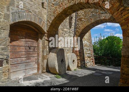 Aperçu d'une allée voûtée dans le village médiéval avec de vieilles pierres contre le mur d'une ancienne maison, San Gimignano, Sienne, Toscane, Italie