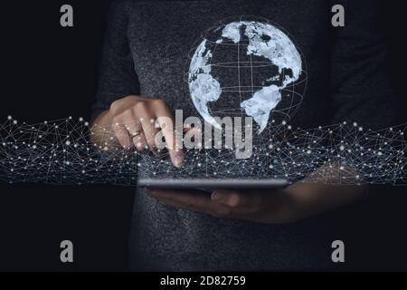 Main touchant la connexion de réseau mondial et les échanges de données sur l'arrière-plan de la planète Terre, concept futuriste