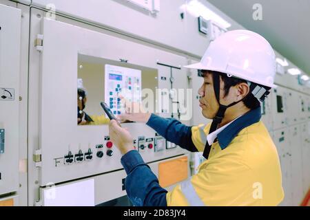 Un ingénieur portant un uniforme jaune et un chapeau de sécurité blanc inspecte les systèmes électriques d'une grande centrale électrique.