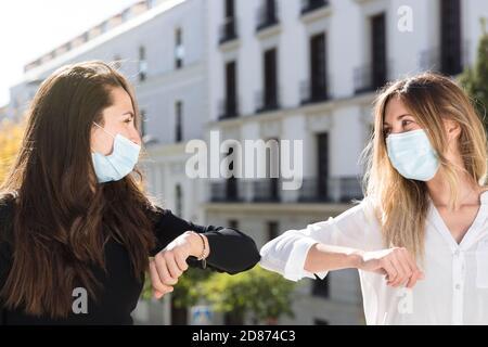 Gros plan de deux filles saluant l'une l'autre avec leurs coudes. Ils sont dans la rue et portent des masques chirurgicaux. Concept de distanciation sociale et n
