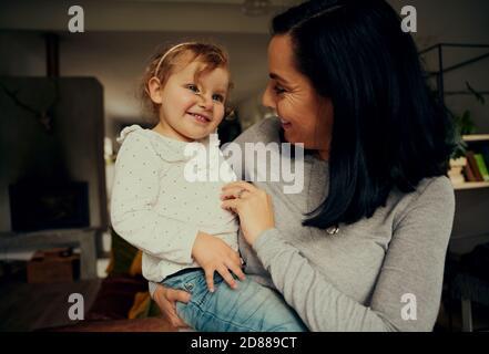 Mère et fille gaies jouant et riant à cause de chatouilles se tenir dans le salon à la maison