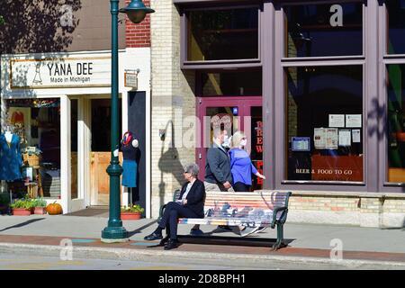 Traverse City, Michigan, États-Unis. Un couple portant un masque facial pendant la pandémie du coronavirus passe devant une femme assise sur un banc le long de Front Street.