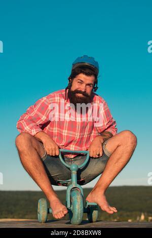 Drôle Crazy hipster gars à vélo. Homme sur un vélo pour enfants. Piste cyclable branchée.
