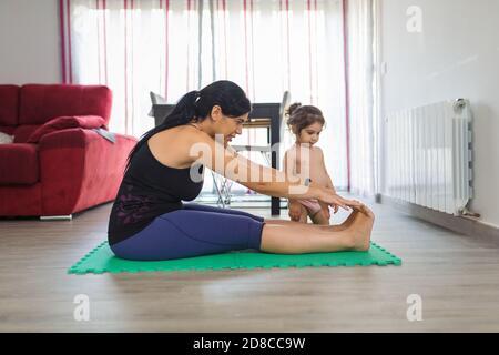 La mère Latino pratique le yoga et les postures de forme physique à la maison sur un tapis avec sa petite fille de deux ans au sol de la salle à manger.