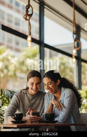 Deux femmes assises dans un restaurant regardant le téléphone mobile. Amis assis dans un café avec un café sur la table regardant le téléphone portable.