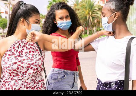 Les jeunes filles portant un masque facial faisant une nouvelle distanciation sociale saluent avec des coudes pour prévenir la propagation du virus corona. Covid 19 et concept d'amitié