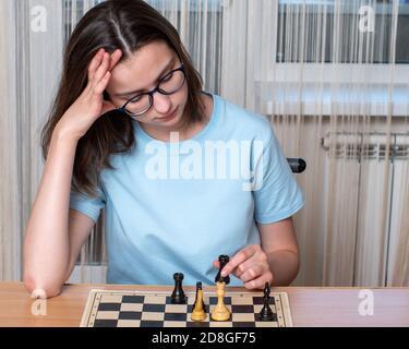 Caucasienne fille avec des lunettes pensant jouer aux échecs, jouant aux échecs à la maison pendant la quarantaine