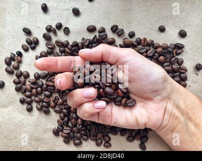 Des grains de café fraîchement torréfiés se déversent des palmiers pliés sur fond de carton brun. Concept de grains de café parfumés Banque D'Images