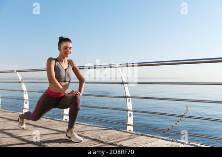 Photo en plein air d'une femme de forme physique attrayante et saine s'entraîner près de la mer, étirant les jambes avant de faire du jogging