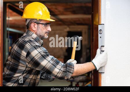 Le travailleur de menuisier au travail avec un tournevis, répare et installe le cadre de porte d'une pièce. Industrie de la construction. Menuiserie. Banque D'Images