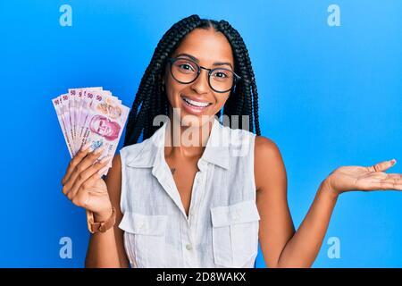 Belle femme hispanique détenant 50 pesos mexicains de billets célébrant la réussite sourire heureux et expression du gagnant avec main levée Banque D'Images
