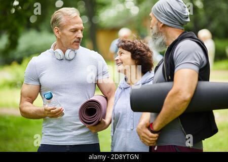 Deux hommes et femmes matures sportifs se tenant ensemble dans le parc discuter de quelque chose avant de faire l'exercice