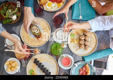 groupe de personnes tenant des baguettes et goûtant la table de nourriture asiatique avec divers types de nourriture chinoise, des rouleaux plats, des sushis, de la salade, des sandwichs