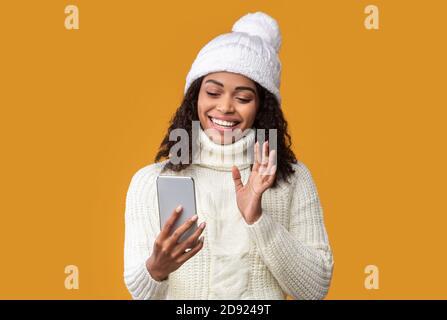 Bonne femme noire effectuant un appel vidéo à l'aide d'un téléphone portable Banque D'Images