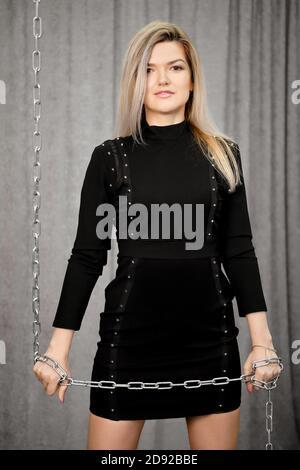 Femme blonde en robe noire tient la chaîne métallique dans les mains