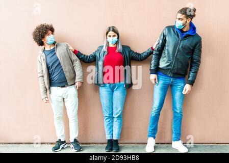un groupe heureux d'amis portant un masque facial protecteur qui garde les distances sociales après la réouverture du verrouillage. deux hommes et une femme les écartent