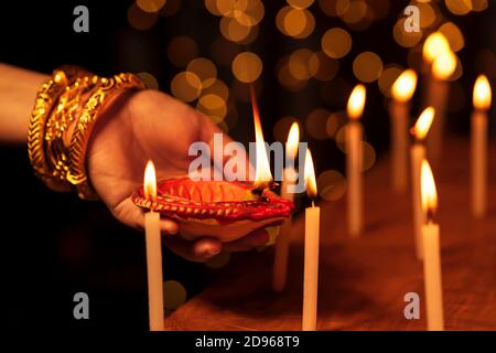 Femme au foyer indien ou femme mariée portant des bijoux traditionnels en or, éclairant des bougies avec une diya d'argile ou une lampe à huile dans une main à un temple sur Diwali Nigh