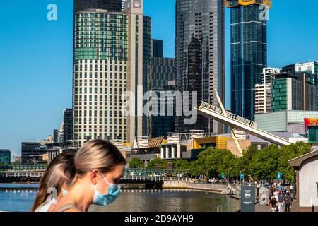 Des personnes masquées marchent devant les gratte-ciel de Melbourne.