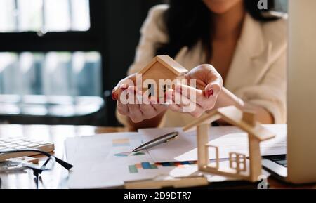 Agent immobilier avec modèle de maison sur hans offre maison. Assurance de biens et concept de sécurité