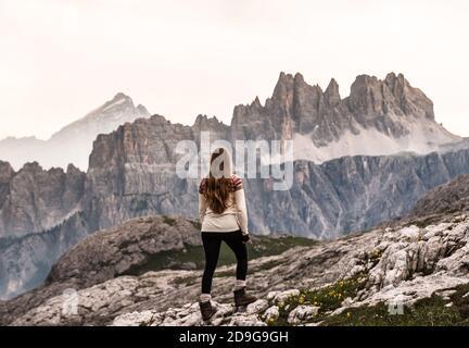une fille regardant le coucher du soleil dans les dolomites faire les montagnes brillent