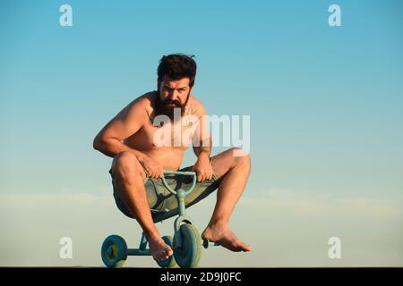 Drôle d'homme sur un vélo. Un homme fou et émotif sur un vélo pour enfants. Un fou qui fait du vélo.